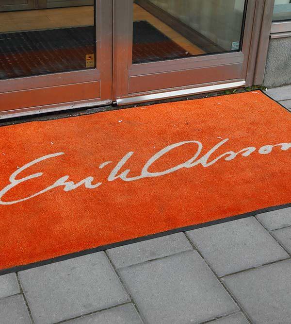 Stockholm, Sweden - July 7, 2016: Orange carpet outside the entrance to real estate broker Erik Olsson's office at the street Sveavagen.